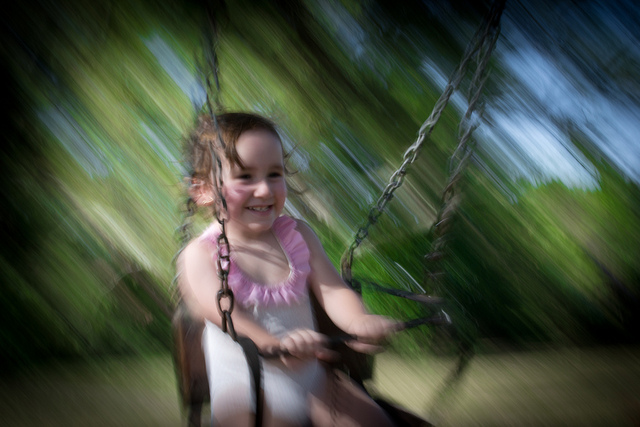 Girl playing on a swing - Photo by Gustavo Devito